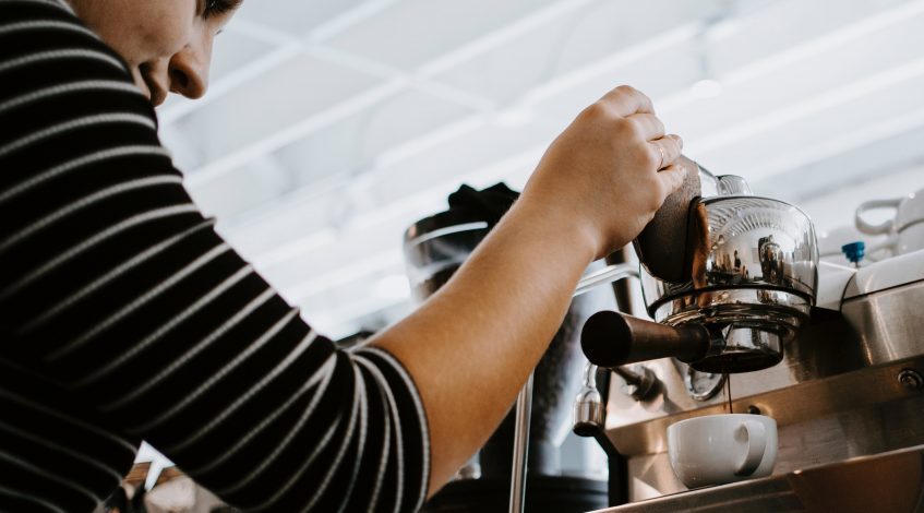 Image of a woman holding down a espresso machine, pouring coffee into the cup.