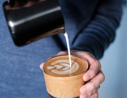 Image of milk being poured into a coffee.